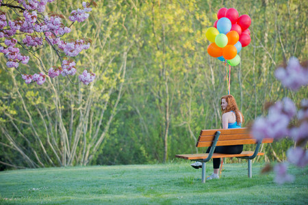 chillout: Teenage girl sitting on park bench with balloons