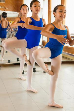 exerting: Ballerinas practising at the barre in ballet school