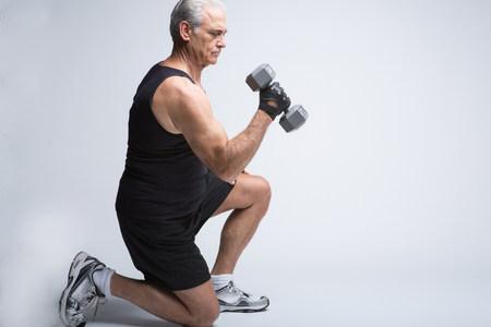 levantar peso: Senior hombre en ropa deportiva levantamiento de brócoli