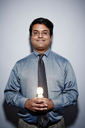 lit image: Studio portrait of businessman with energy saving lightbulb