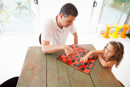 draughts: Father and daughter playing draughts