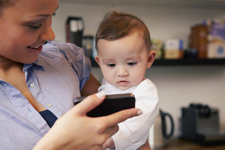 6 12 months: Mother showing baby girl smartphone