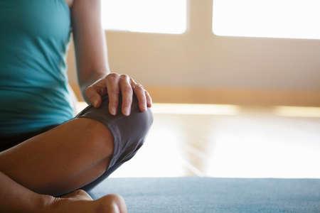 Part body shot of mature woman practicing yoga indoors