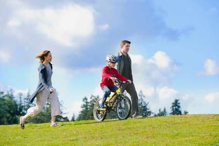 Parents keeping up with son riding bicycle