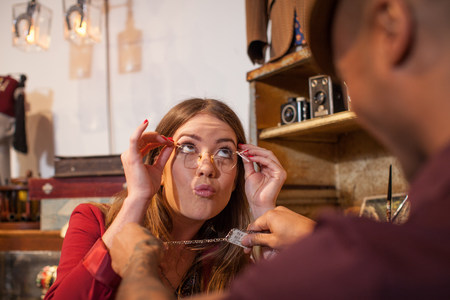 jesting: Woman in vintage shop trying on glasses and pulling faces
