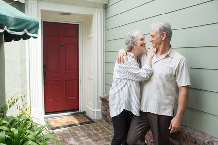 60 65 years: Senior couple smiling together outside house