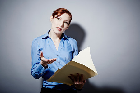 authoritative woman: Studio portrait of young woman holding folder LANG_EVOIMAGES