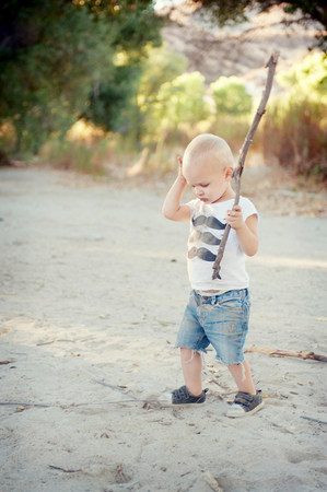 casual clothing 12 year old: Young male toddler with stick