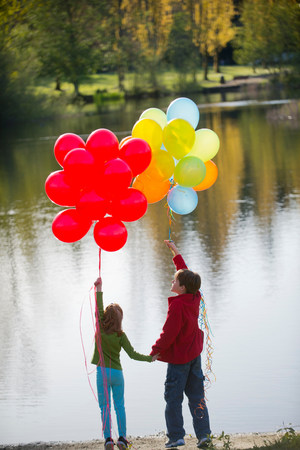 Brother and sister with bunches of balloons in park LANG_EVOIMAGES
