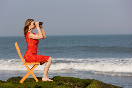 Mature woman sitting on chair on beach with binoculars