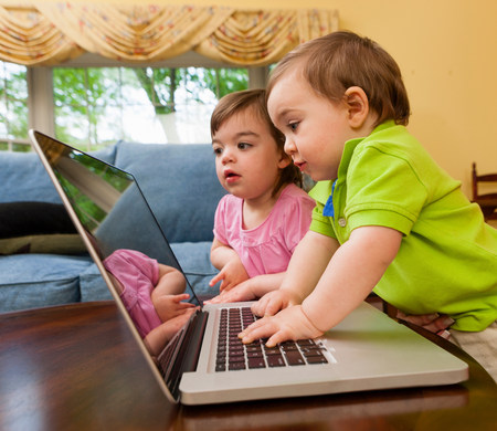 level playing field: Two young toddlers playing with laptop