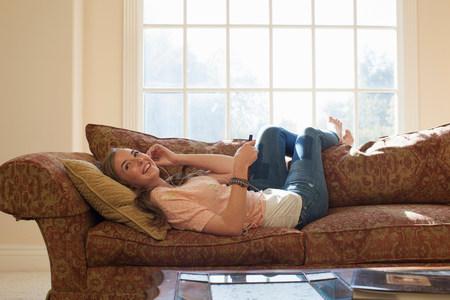 chillout: Teenage girl lying on sofa with earphones