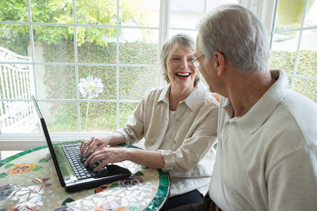 conservatories: Senior couple using laptop in conservatory