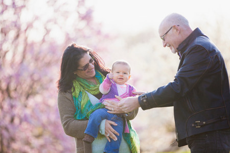 new age: Grandparents and granddaughter in garden LANG_EVOIMAGES