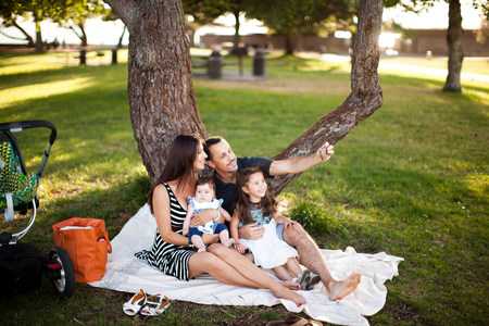Family with two children sitting on picnic blanket