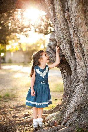 Portrait of girl touching tree trunk