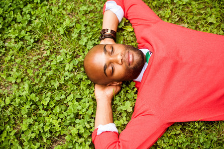 Portrait of young man lying on grass