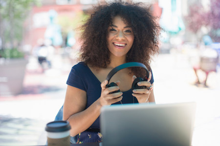 Young woman holding headphones at sidewalk cafe