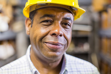 american field service: Close up portrait of man in stockroom wearing hard hat LANG_EVOIMAGES