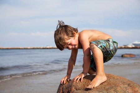 Boy crouching on rock on beach