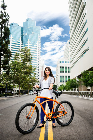 Young woman standing road with bicycle in city,smiling