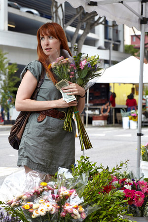 Mid adult woman buying flowers from stall in city