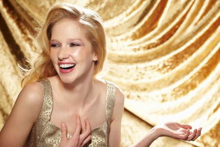 Candid portrait of young woman in front of gold curtain