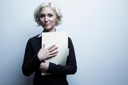 Studio portrait of businesswoman holding file LANG_EVOIMAGES
