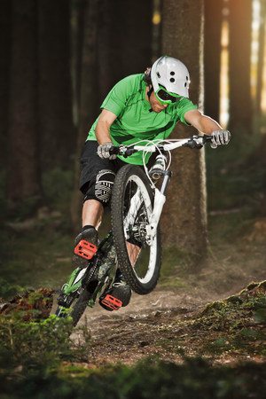Mountain biker riding on back wheel through forest