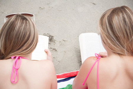 untruth: Young women reading books on beach