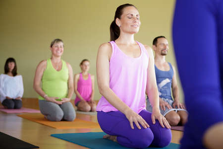 all under 18: Mixed age group practicing yoga in exercise studio