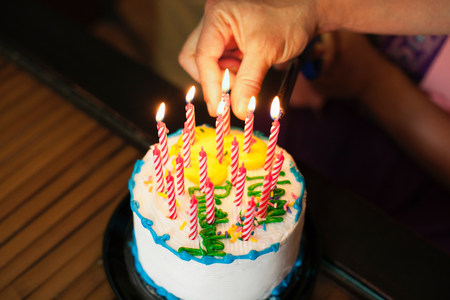 age 10 12 years: Hand putting candles into cake LANG_EVOIMAGES
