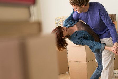 Couple dancing together whilst moving house