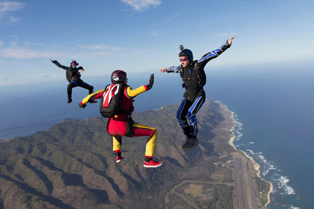 legs wide open: Three formation skydivers free falling LANG_EVOIMAGES