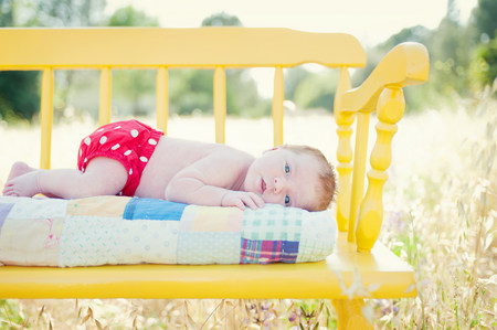 nappy new year: Newborn baby girl lying on yellow bench in field LANG_EVOIMAGES