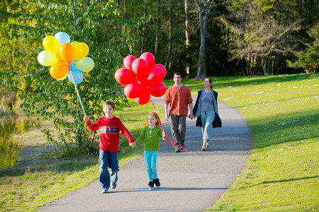 Family walking through park with bunches of balloons LANG_EVOIMAGES