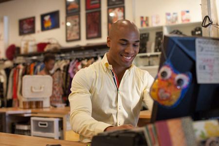 skinhead: Shopkeeper using computer in vintage shop