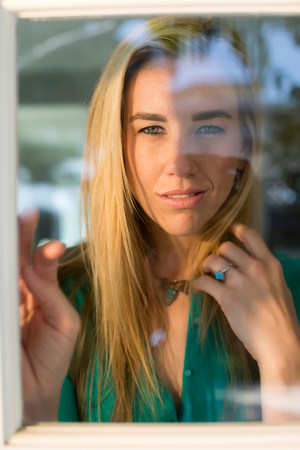 mirroring: Portrait of young woman looking through window,hand in hair