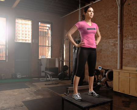engrossed: Young woman standing on table in gym LANG_EVOIMAGES