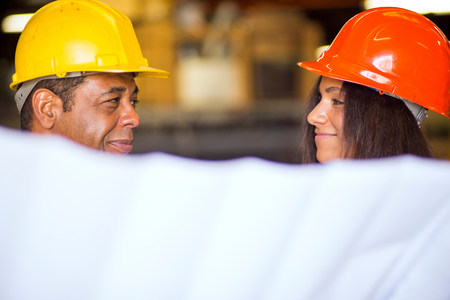 Man and woman in warehouse holding blueprint
