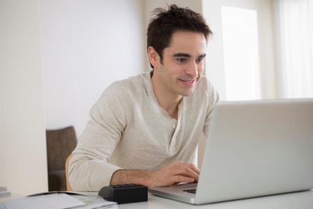 Mid adult man using laptop,smiling