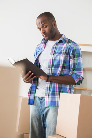 cardboard only: Mid adult man reading book surrounded by cardboard boxes