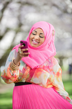 Portrait of young female with matching mobile and  headscarf LANG_EVOIMAGES