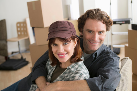 begin: Portrait of couple resting on chair whilst moving home