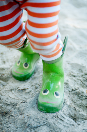 Legs of young male toddler wearing smiley wellington boots