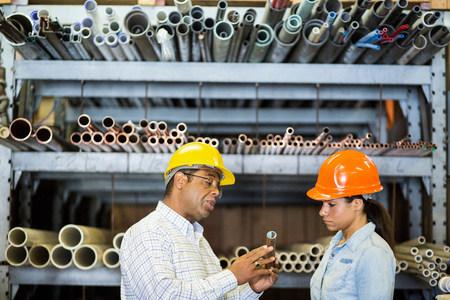 sinergia: Dos trabajadores de almacén mirando tubería de cobre LANG_EVOIMAGES