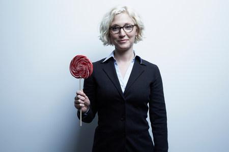 silliness: Studio portrait of blond businesswoman with red lollipop
