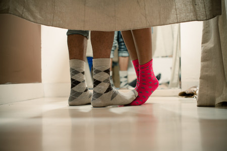 discretion: Young couple wearing socks in changing room,low section
