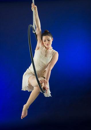 exerting: Aerialist poised on hoop against blue background