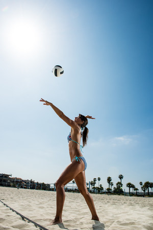 Female beach volleyball player hitting ball